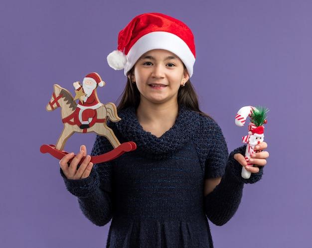 Heureuse petite fille en robe tricotée portant un bonnet de noel tenant des jouets de noël souriant joyeusement debout sur un mur violet