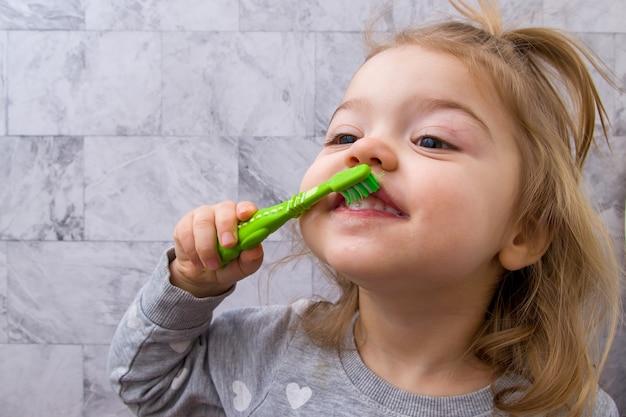 Heureuse petite fille se brosse les dents dans la salle de bain. concept de soins dentaires