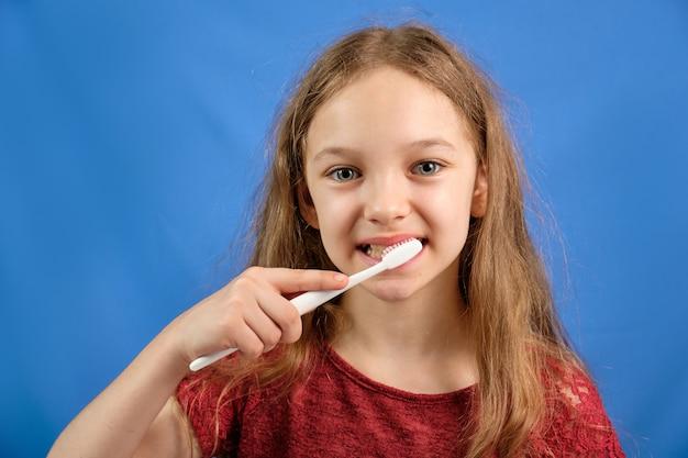 Heureuse petite fille se brosser les dents avec une brosse à dents sur un espace bleu.