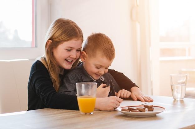 Heureuse petite fille et son frère écrivant sur papier