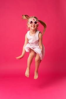 Heureuse petite fille souriante dans des lunettes de soleil sur fond rose