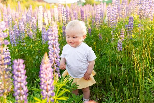 Heureuse petite fille souriante en plein air. belle jeune fille blonde reposant sur le champ d'été avec fond vert de fleurs sauvages en fleurs. enfant heureux gratuit, concept d'enfance. enfant en bas âge positif
