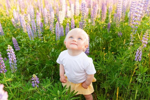 Heureuse petite fille souriante en plein air jeune bébé fille reposant sur un champ d'été avec des fleurs sauvages en fleurs
