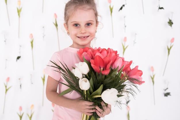 Heureuse petite fille tenant des fleurs