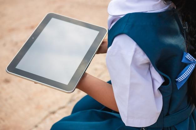 Heureuse petite fille tenant une tablette pc à l'extérieur dans le parc de l'été