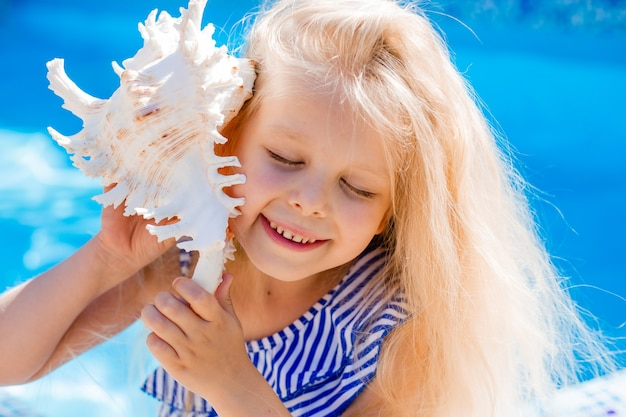 Heureuse petite fille tient un coquillage près de son oreille dans le contexte de la mer