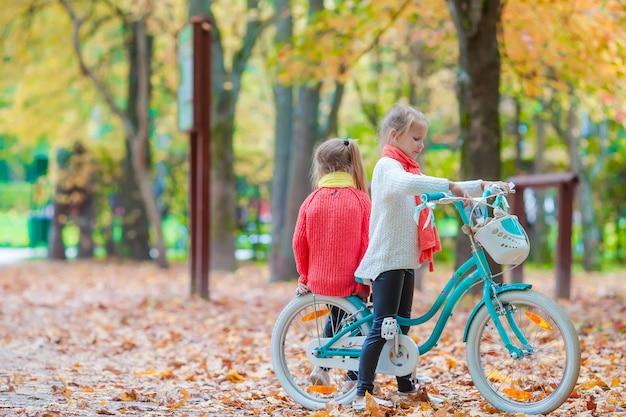Heureuse petite fille à vélo à la belle journée d'automne en plein air