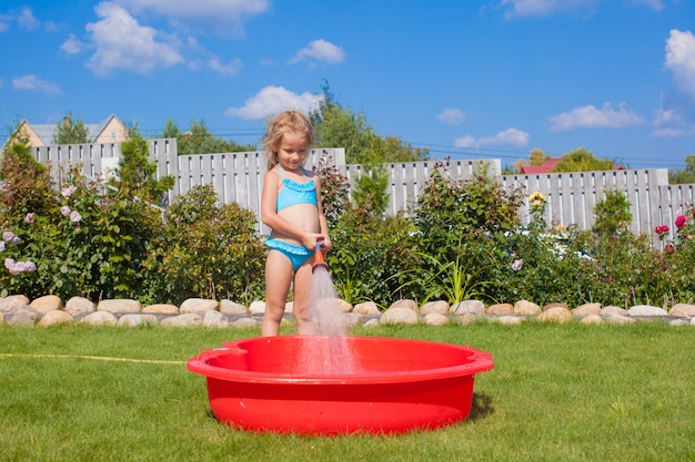 Heureuse petite fille verser de l'eau d'un tuyau d'arrosage et rire