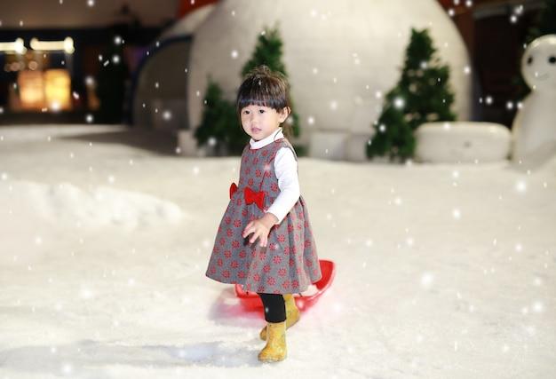 Heureuse petite fille vêtue d'une veste rouge - grise s'amuse dans la neige, l'hiver.