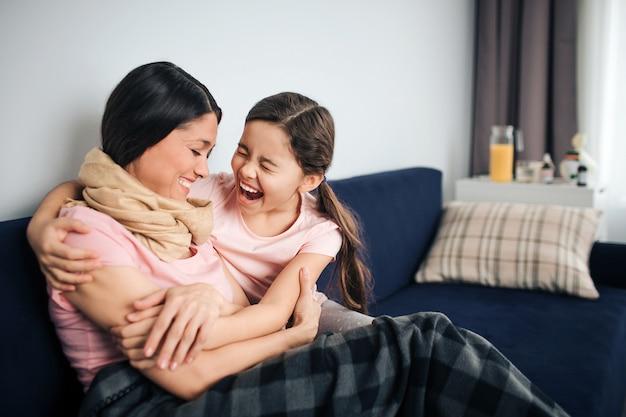 Heureuse et positive jeune femme assise avec sa fille sur le canapé dans la chambre