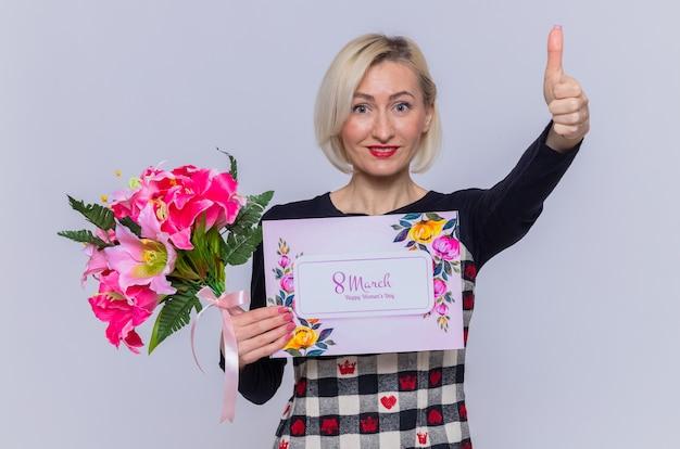 Heureuse et positive jeune femme tenant une carte de voeux et un bouquet de fleurs