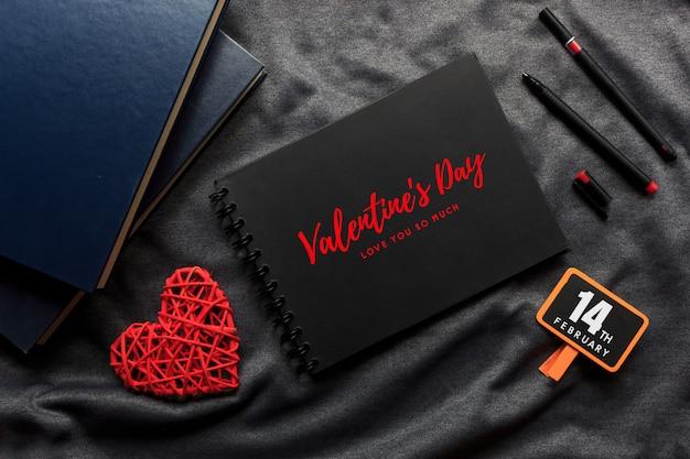 Heureuse saint valentin concept, livre noir, coeur rouge et stylo sur toile grise