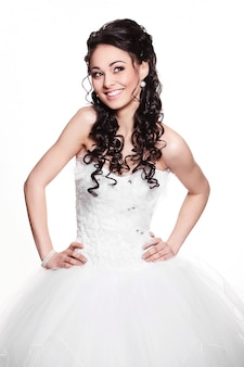 Heureuse sexy belle mariée brune fille en robe de mariée blanche avec coiffure et maquillage lumineux sur fond blanc