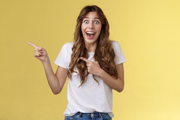 Heureuse sincère joyeuse jeune femme surprise voir la célébrité perdre la parole regarder excité incroyable incroyable chance fasciné pointer l'index laissé bouche ouverte abasourdi ravi fond jaune