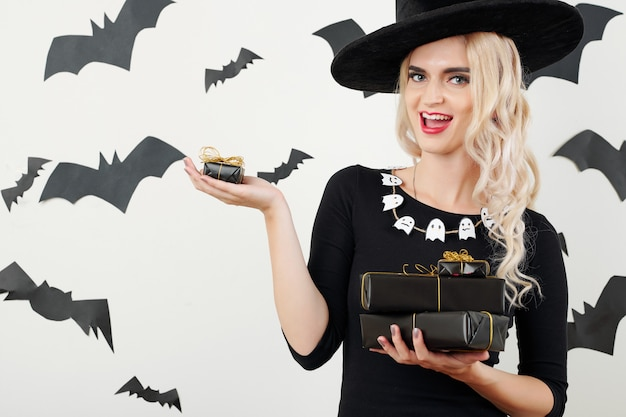 Heureuse sorcière avec des cadeaux et des cadeaux d'halloween