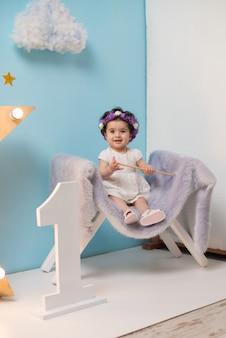 Heureuse souriante douce petite fille assise sur le fauteuil avec une étoile brillante