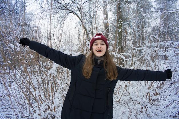 Heureuse souriante mignonne belle jeune adolescente séduisante aux longs cheveux blonds aux yeux verts sur fond violet bleu flou naturel dans la forêt d'hiver enneigée et givrée. fille s'amuse en plein air