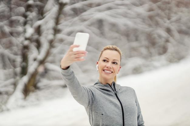 Heureuse sportive debout dans la nature lors d'une journée d'hiver enneigée et prenant un selfie pour les médias sociaux.