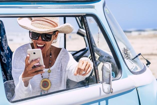 Heureuse et surprise belle jeune femme avec des vêtements à la mode et un accessoire regarde son téléphone surpris avec joie