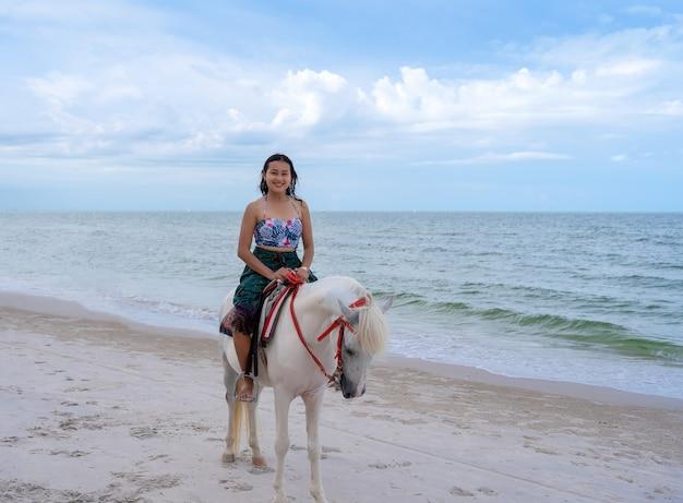 Heureuse touriste asiatique en tenue de plage chevauchant un cheval blanc sur la plage de sable de la plage de huahin avec une mer bleue et un ciel nuageux, détendez-vous en vacances en thaïlande