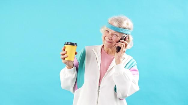Heureuse vieille femme aux cheveux gris parle sur un téléphone portable, portant un survêtement. âge, sport.