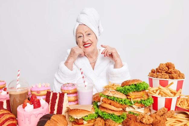 Heureuse vieille grand-mère profite d'une journée de repas de triche entourée de malbouffe