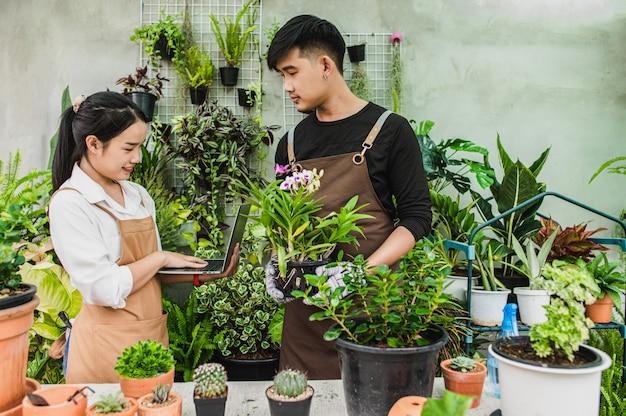 Heureusement, un jeune couple de jardiniers asiatiques portant un tablier utilise du matériel de jardin et un ordinateur portable pour prendre soin de