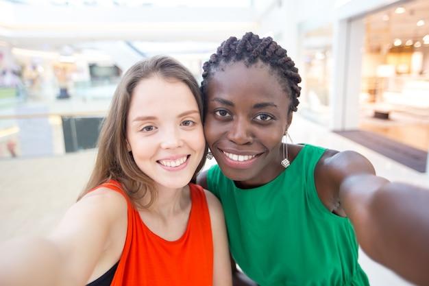 Heureuses amies féminines multiethniques prenant la selfie
