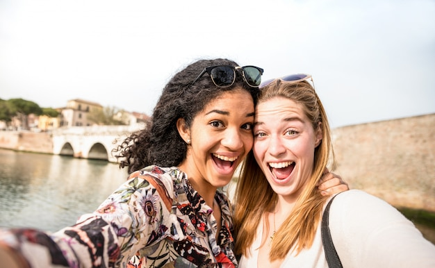 Heureuses copines multiraciales prenant selfie et s'amusant à l'extérieur
