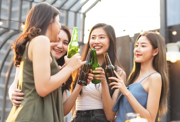 Heureuses femmes asiatiques tenant des bouteilles de bière