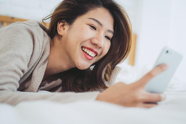 Heureuses femmes asiatiques utilisent un téléphone intelligent sur le lit le matin