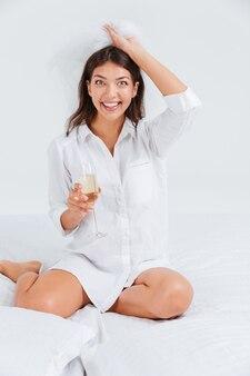 Heureuses femmes souriantes portant un voile de mariée et tenant un verre avec du champagne isolé
