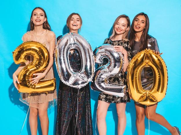 Heureuses filles magnifiques dans des robes de soirée sexy élégantes tenant des ballons d'or et d'argent 2020