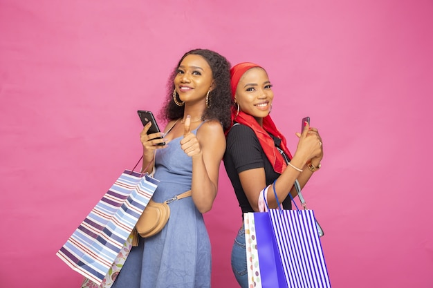 Heureuses jeunes femmes africaines posant avec des sacs à provisions avec les pouces vers le haut