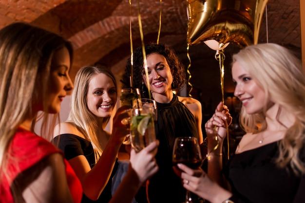 Heureuses jeunes femmes ayant une fête d'anniversaire en riant, en dansant, en chantant, en profitant de la nuit dans un restaurant élégant.