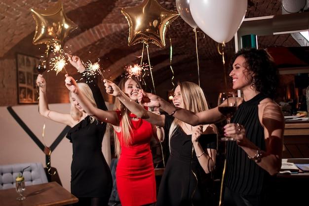 Heureuses jeunes femmes tenant des feux d'artifice, des ballons, des verres de vin célébrant des vacances au restaurant avec un intérieur gothique.
