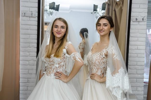 Heureuses mariées en robes de mariée posant dans le salon