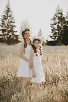 Heureuses soeurs en robes blanches avec des couronnes florales et des tresses de style boho en été dans un champ
