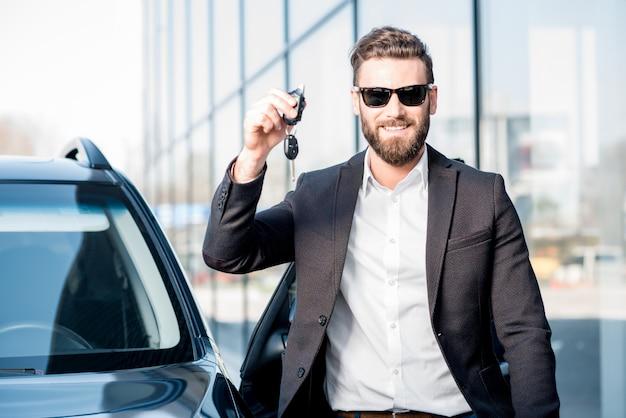 Heureux acheteur tenant des clés près de la voiture devant le bâtiment moderne d'avtosalon