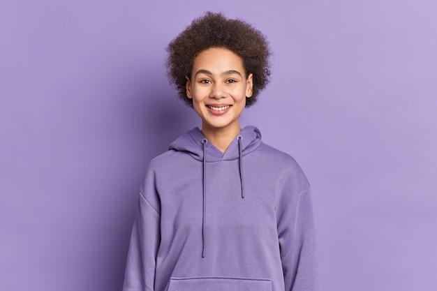 Heureux adolescent ethnique avec des sourires de cheveux afro porte positivement un sweat à capuche violet étant de bonne humeur.