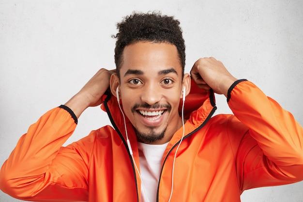 Heureux adolescent masculin élégant aux cheveux bouclés, porte un anorak et une capuche, écoute la piste préférée dans les écouteurs, regarde joyeusement