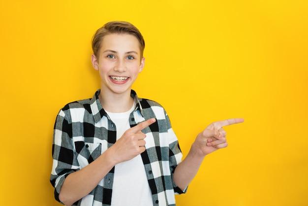 Heureux adolescent masculin heureux pointe dans le coin supérieur droit, a un sourire agréable à pleines dents