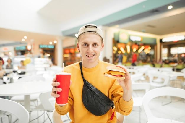 Heureux adolescent tient un verre de boisson froide et un sandwich