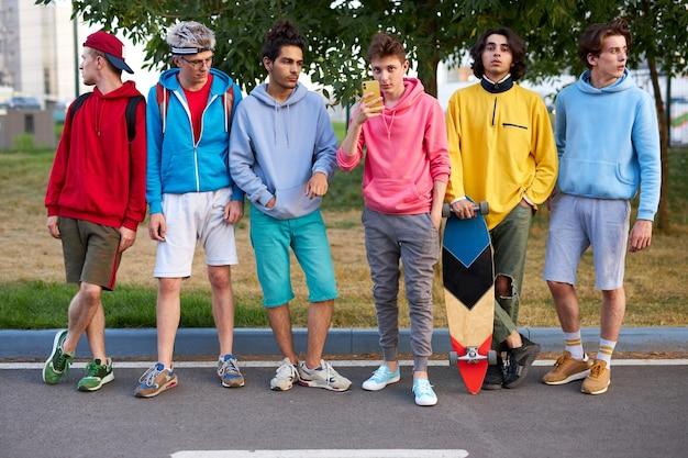 Heureux adolescents garçons skateboarders s'amusent en plein air