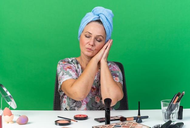 Heureux adulte caucasien femme aux cheveux enveloppés dans une serviette assis à table avec des outils de maquillage avec les mains ensemble