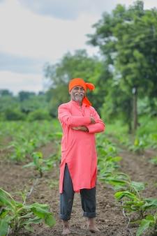 Heureux agriculteur indien debout et sourire au champ