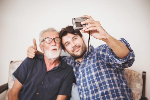 Heureux aîné, fils prend une photo avec son oncle, famille heureuse avec un style de vie d'appareil photo numérique.