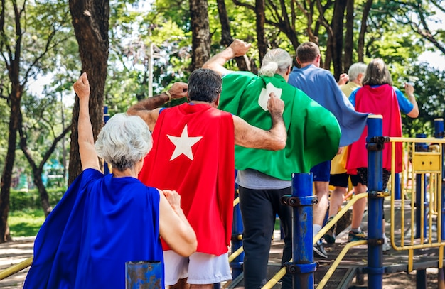 Heureux aînés portant des costumes de super-héros dans une aire de jeux