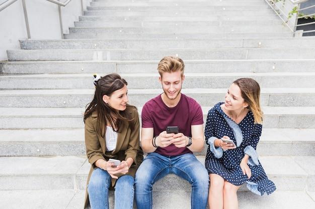 Heureux ami assis sur l'escalier avec smartphone