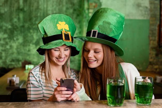 Heureux amies célébrant st. patrick's day avec smartphone au bar
